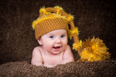 Newborn in knitted winter hat on a beige background. Stock Photo