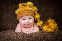 Newborn in knitted winter hat on a beige background. Stock Image