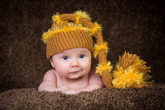 Newborn in knitted winter hat on a beige background. Stock Photography