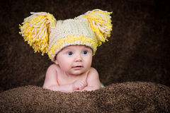 Newborn in knitted winter hat on a beige background. Royalty Free Stock Photo