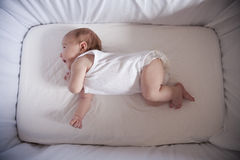 Newborn laughing in cradle Stock Photo