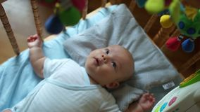 Newborn lies in the blue bed with mobile and toys. The kid actively reacts to the toy, pulls the pens and legs stock footage