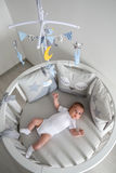 Newborn lies in the round white bed with mobile Royalty Free Stock Photo