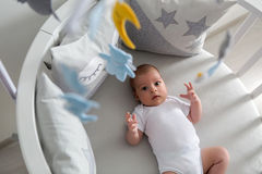 Newborn lies in the round white bed with mobile Royalty Free Stock Photos