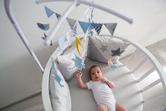 Newborn lies in the round white bed with mobile Royalty Free Stock Photography