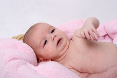 Newborn little girl on pink towel Stock Photos