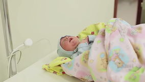 Newborn lying on the swaddling table in the hospital. Little baby after birth stock video