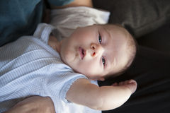 Newborn on man arms looking Royalty Free Stock Photo