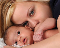 Newborn and Mom. Close-up of an attractive mom snuggling with her bright-eyed newborn son Royalty Free Stock Photo