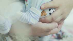 Newborn on mom's hands. Newborn on moms hands close-up of moms hands and toddlers legs slow motion stock footage