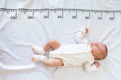 A newborn 2 month baby in white sleeps on a bed on which a measuring ruler for growth is drawn
