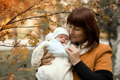 Newborn on the mother hands in autumn Royalty Free Stock Photography