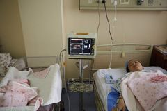 A newborn and mother under monitoring by machine. Chinese baby girl and the mom just delivering laying on hospital bed, under monitoring Stock Image