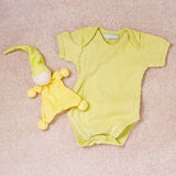 Newborn onesie outfit and toy clown Royalty Free Stock Images