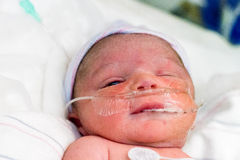Newborn On Oxygen. A newborn infant in the NICU. He has an oxygen tube in his nose and a drainage tube in his mouth. He has one eye open and is looking at the stock photo