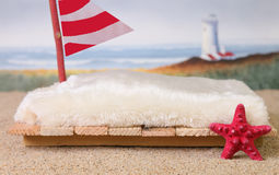 A newborn photography prop of a raft at the ocean. A handmade prop for studio photography of a wooden raft with a faux fur bedspread, a red and white sail, a Royalty Free Stock Photo