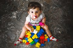 Newborn play building blocks - colorful toy bricks - above view. Of a baby playing with toy bricks - little child play on floor royalty free stock images