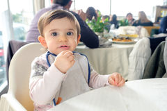Newborn restaurant baby bib high chair table eating chew cloth.  Royalty Free Stock Photography