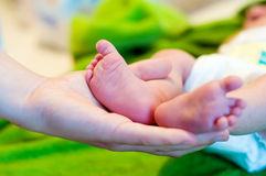 Newborn's feet. Mother's hand holds newborn feet stock photos