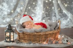 Newborn in Santa Claus clothes. Sleeping in a basket Royalty Free Stock Images