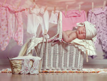 Newborn sleep in the basket after helping her mother in the laundry washing Stock Photo