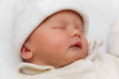 Newborn baby girl (exactly 2 hours old). Newborn sleeping baby girl wrapped in a fleece bodysuit and hat. Taken at precisely 2 hours old. Focus on eye Royalty Free Stock Image