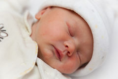 Newborn baby girl (exactly 2 hours old). Newborn sleeping baby girl wrapped in a fleece bodysuit and hat. Taken at precisely 2 hours old. Focus on eye Stock Image