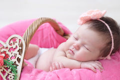 Newborn sleeping in basket, baby girl lying in pink blanket, cute child. Daughter announcement Royalty Free Stock Images