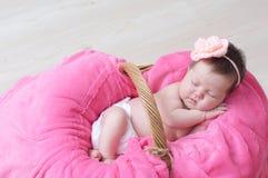 Newborn sleeping in basket, baby girl lying in pink blanket, cute child. Daughter announcement Stock Photo