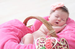 Newborn sleeping in basket, baby girl lying in pink blanket, cute child. Daughter announcement Royalty Free Stock Photos