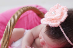 Newborn sleeping in basket, baby girl lying in pink blanket, cute child, daughter announcement. Knitted flower on head Royalty Free Stock Photos