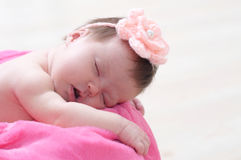 Newborn sleeping in basket with knitted flower on head, baby girl lying on pink blanket, cute child Stock Image