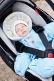 Newborn sleeping in the car seat. Newborn boy sleeping in the car seat outdoors royalty free stock photography