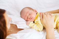 Newborn sleeping child. In the hands of mother. Co-sleeping mother and baby child. Young beautiful mother recovering after childbirth Royalty Free Stock Photos