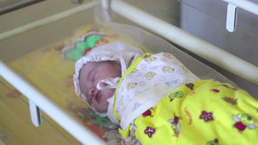 A newborn is sleeping in the children bed in the hospital. Babe wrapped in swaddling clothes stock video footage