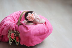 Newborn sleeping. Infant baby girl closeup lying on pink blanket in basket decorated with wooden heart Royalty Free Stock Photo