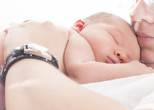 Newborn sleeping in mothers arms Stock Images