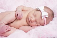 Newborn sleeping naked on her side. stock image
