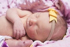 Newborn sleeping naked on her side. royalty free stock photography