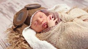 Newborn sleeping with old pilot`s helmet stock footage