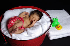 Newborn sleeping in tub Stock Images