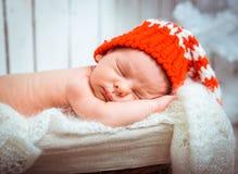 Newborn sleeps in santa hat Stock Photos