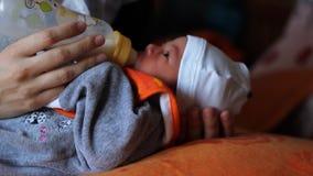 Newborn Sucking Milk of Bottle. Newborn is suckling milk of the baby bottle stock video