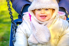 Newborn swing baby smile winter fun play park outdoor playground Royalty Free Stock Images