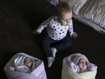 The newborn twins in a blanket with his year-old sister Stock Photo