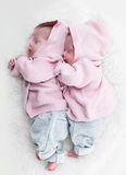 Newborn twins sisters sleeping on white fur together in cute pink sweaters Stock Photo