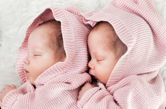 Newborn twins sisters sleeping on white fur together in cute pink sweaters Royalty Free Stock Image