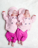 Newborn twins sisters sleeping on white fur, wearing pink sweaters Stock Image