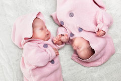 Newborn twins sisters sleeping on white fur, wearing pink sweaters Stock Images