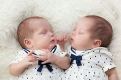 Newborn twins sisters sleeping on white fur, wearing sailor dresses. Stock Photography